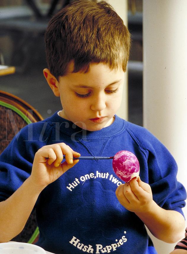 Boy coloring Easter egg #2. Family. Douglaston NY.