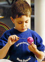 Boy coloring Easter egg #2. Family. Douglaston NY.