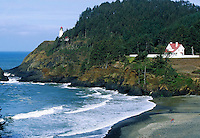 Heceta Head Lighthouse along rugged Oregon coast with Pacific Ocean and land features in foreground. Oregon, Oregon coastline.