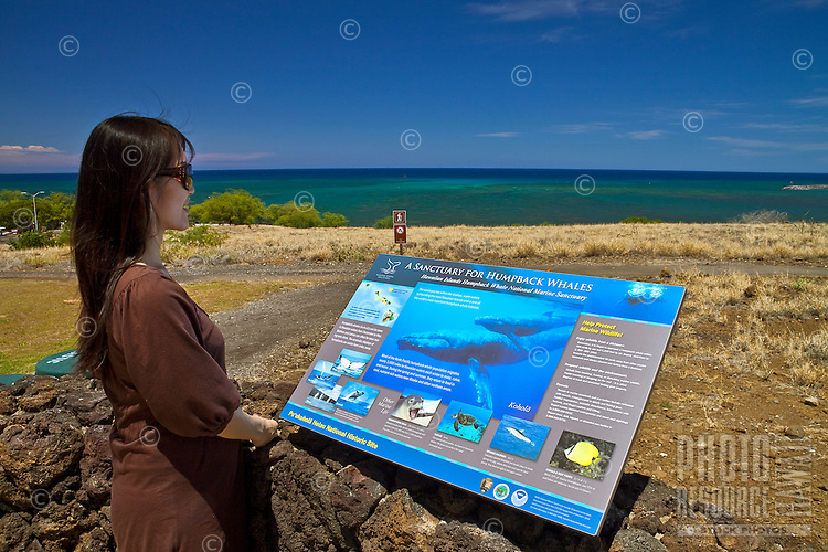 "A smiling female visitor looking at ""A Sancutary For Humpback Whales"" educational sign at Pu'ukohola Heiau National Historic Site, Kawaihae, Kohala, Big Island."