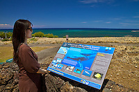 "A smiling female visitor looking at ""A Sancutary For Humpback Whales"" educational sign at Pu'ukohola Heiau National Historic Site, Kawaihae, Kohala, Big Island."