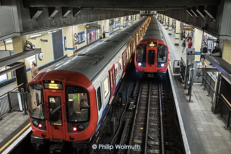 District Line trains at Aldgate East tube station, London..