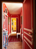 A view down a red-painted corridor which opens into a further corridor painted yellow, with doors outlined in white