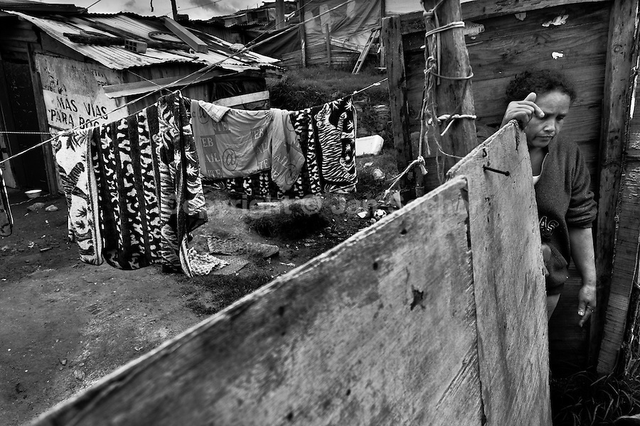 A displaced woman from Meta department stands behind the chipboard barrier in the slum of Ciudad Bolívar, Bogota, Colombia, 28 May 2010. With nearly fifty years of armed conflict, Colombia has the highest number of civil war refugees in the world. During the last ten years of the civil war more than 3 million people have been forced to abandon their lands and to leave their homes due to the violence. Internally displaced people (IDPs) come from remote rural areas, where most of the clashes between leftist guerrillas FARC-ELN, right-wing paramilitary groups and government forces takes place. Displaced persons flee in a hurry, carrying just personal belongings, and thus they inevitably end up in large slums of the big cities, with no hope for the future.