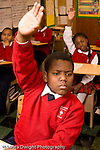 K-8 Parochial School Bronx New York Grade 4 boy with hand raised for attention in class vertical