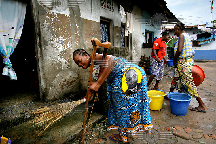 A disabled woman wearing a dress emblazoned with a picture of President Joseph Kabila leans on a crutch while cleaning her doorstep in a slum area.