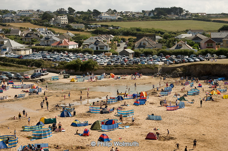Cars parked above the beach in the village of Trevone in North Cornwall.