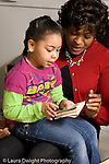 Education preschool 4 year olds female teacher with girl seated on her lap looking at and talking about folded drawing the girl holds vertical