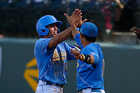 Brian Carroll #24 of the UCLA Bruins is greeted by teammate Trent Chatterton #8 after scoring a run against the California Golden Bears at Jackie Robinson Stadium on March 23, 2013 in Los Angeles, California. (Larry Goren/Four Seam Images)