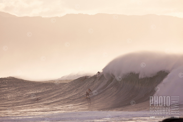 Surfers riding big waves at sunset with Mount Kaala in the background at North Shore, Oahu