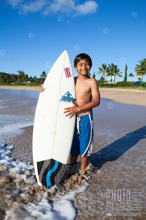 A young local surfer holds his surfboard at Hanalei Beach, Kaua'i.
