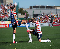 """Carli Lloyd (10) of the USWNT has her shoes """"shined"""" by teammate Heather Mitts (2) after she scored a goal during a friendly match at Sahlen's Stadium in Rochester, NY.  The USWNT defeated Costa Rica, 8-0."""