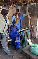 Cashew Nut Buyer Takes a Phone Call While Weighing Nuts,  Fass Njaga Choi, The Gambia.