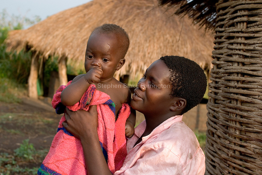 Empowering Victims of War- A young family takes in the morning light. Canaan Family Farm lends land to displaced people from the Northern conflict to have them learn the benefits of work and empowerment. Rwakayata, Masindi, Uganda, Africa. December 2005 © Stephen Blake Farrington