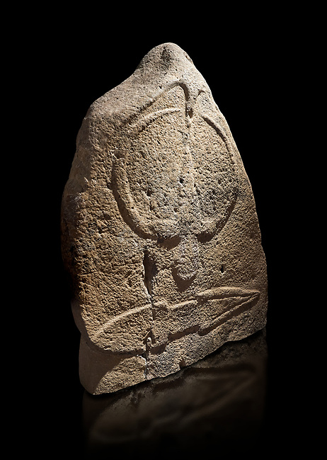 Late European Neolithic prehistoric Menhir standing stone with carvings on its face side. The representation of a stylalised male figure starts at the top with a long nose from which 2 eyebrows arch around the top of the stone. below this is a carving of a falling figure with head at the bottom and 2 curved arms encircling a body above. at the bottom is a carving of a dagger running horizontally across the menhir. Excavated from Barilli I site,  Laconi. Menhir Museum, Museo della Statuaria Prehistorica in Sardegna, Museum of Prehoistoric Sardinian Statues, Palazzo Aymerich, Laconi, Sardinia, Italy. Black background.