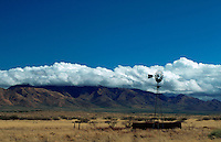 Scenic western landscape of a ranch windmill and desert plain under a wide sky with the Dos Cabezas Mountains in the background. Arizona.