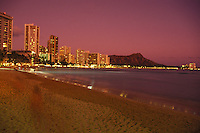 The lights of Waikiki and the silhouette of Diamond Head as seen from Waikiki Beach shortly after sunset.