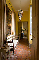A terracotta tiled corridor is simply furnished with a rustic bench and an unrestored lantern