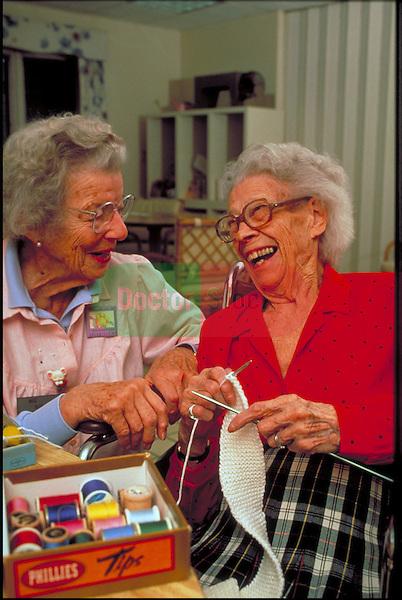 laughing elder women doing needle crafts in nursing home