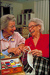 laughing elder women doing needle crafts in nursing home