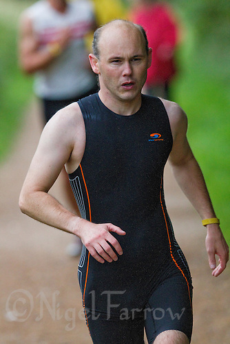 17 AUG 2011 - NORWICH, GBR - Iain Dawson concentrates as he tries to recognise features of a course and avoid obstacles during a Tri-Anglia club aquathlon at Whitlingham Outdoor Centre. Through reconnoitering courses in advance with his wife Jill and then memorising landmarks they find he can race independently in shorter, less crucial, events though can have difficulty with low branches and obstacles on paths such as dogs  (PHOTO (C) NIGEL FARROW)