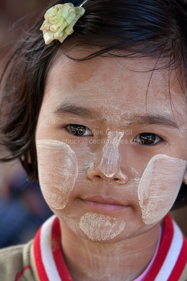 Myanmar, Burma.  Mingun, near Mandalay.  Young Burmese Girl.  She is wearing thanaka paste on her face, a cosmetic sunscreen.