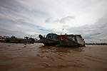 Two boats are anchored alongside each other on the Hau River in the Mekong Delta, south Can Tho, Vietnam. Sept. 30, 2011.