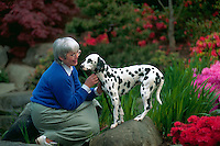 Middle-aged woman outside with her dalmatian.