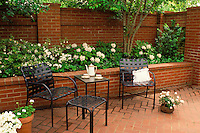 Formal patio in backyard garden set for tea for two with flower bed planted with ivy and azaleas and potted plants