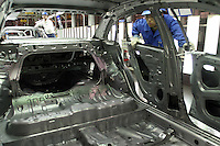 A Chinese worker inspects the interior shell of a Buick at the Shanghai General Motors (SGM) plant in Shanghai, China. SGM is a joint-venture between General Motors and the Shanghai Automotive Industry Corporation also known as SAIC..