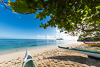 Under the shade of a tree at Waimanalo Beach, looking out at two kayakers on Waimanalo Bay, with Manana and Kaohikaipu Islands further in the distance, Windward O'ahu.