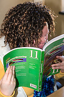 South Africa, Cape Town.  Visually-impaired Albino Student Reading Workbook.  Athlone School for the Blind.