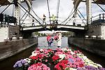 """Foto: VidiPhoto<br /> <br /> AMSTERDAM - Na het frisse en natte pinksterweekend is het hoog tijd voor het zomergevoel, want er is beter weer in aantocht. Daarom vaart een kleurrijke hortensiaboot woensdag door de Amsterdamse grachten. Kwekers delen spontaan honderden bloeiende hortensia's uit aan dolenthousiaste woonbootbewoners en voorbijgangers. Doel is om een groene, gezonde leefomgeving te bevorderen op woonboten, gevel- en stadstuintjes. De verrassingsactie volgt op de bekendmaking dat het voorjaar van 2021 een van de koudste is van de afgelopen tien jaar. In mei is het normaal al op en top zomer met veel zon en warmte. De bloeiende hortensia's moeten alvast zorgen  voor zomerse sferen."""""""