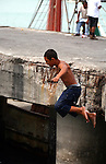 Young Mexican boy jumps off ledge into water below
