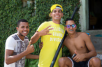 3 Brazilian guys sit on the entrance to their house watching the fans walk past