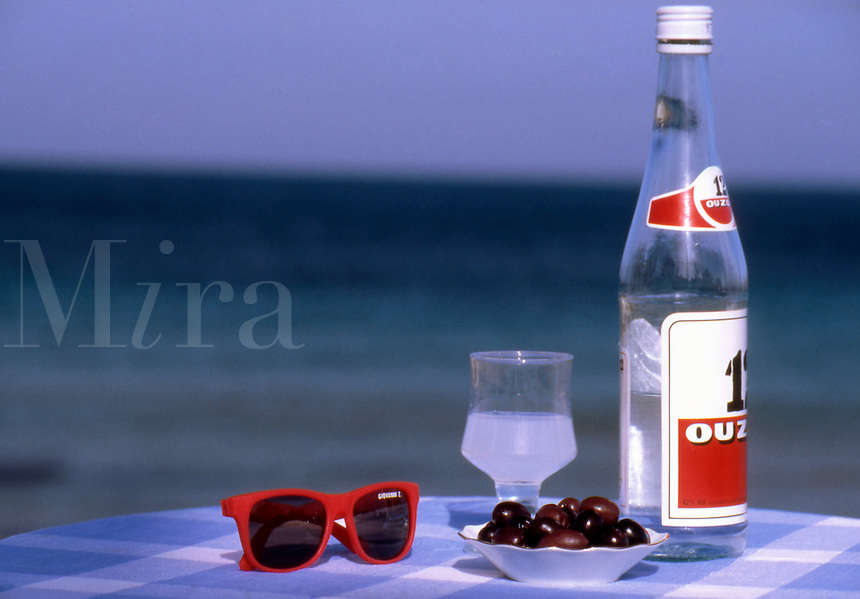 Greece. Bottle and glass of Ouzo, plate of black olives and red sunglasses, on a table by the sea.