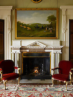 A pair of red velvet armchairs flanks a glowing fire in the entrance hall