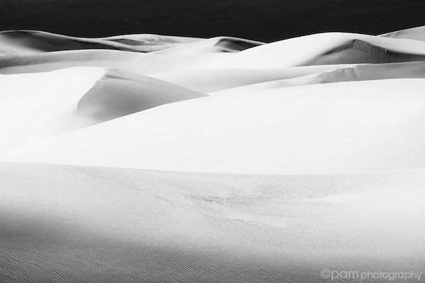 Monochrome image of white sand dunes with black background