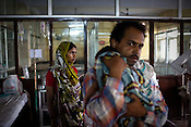 Parents of an ill child are seen with their malnutritioned child at the pediatrics section of the Maharani Laxmibai Medical College in Jhansi, Uttar Pradesh, India. The Indian government spends $1.4 billion a year - on programs that include weighing newborn babies, counseling mothers on healthy eating and supplementing meals, but none of this is yeilding results. According to UNICEF, some 48% of Indian children, or 61 million kids, remain malnourished, the clinical condition of being so undernourished that their physical and mental growth are stunted. Photo: Sanjit Das/Panos for The Wall Street Journal.Slug: IMALNUT