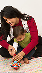 Baby boy 12 months old with mother interested has she shows him how top toy works