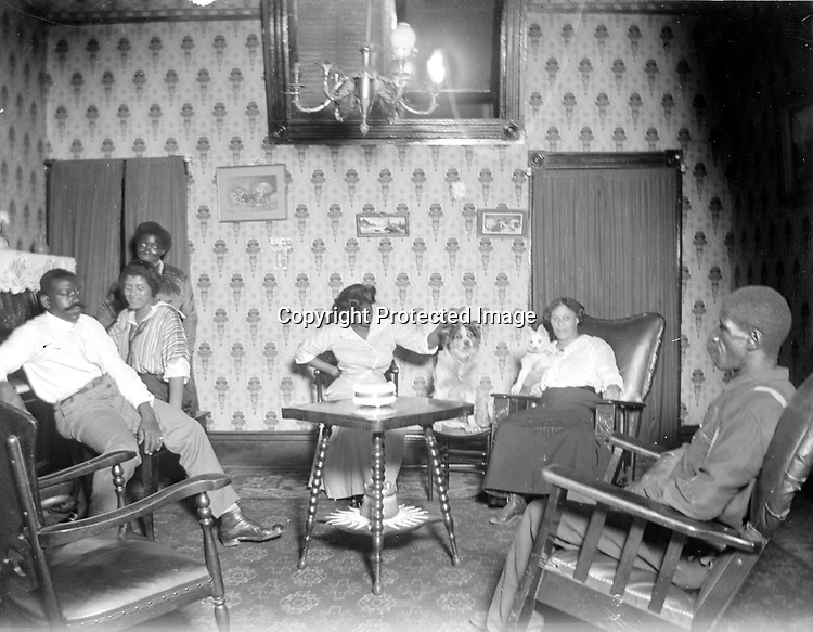 GATHERED IN THE PARLOR. The assortment of chairs and rockers in this high-ceiling room includes a chair for the dog at rear center.<br /> <br /> Photographs taken on black and white glass negatives by African American photographer(s) John Johnson and Earl McWilliams from 1910 to 1925 in Lincoln, Nebraska. Douglas Keister has 280 5x7 glass negatives taken by these photographers. Larger scans available on request.