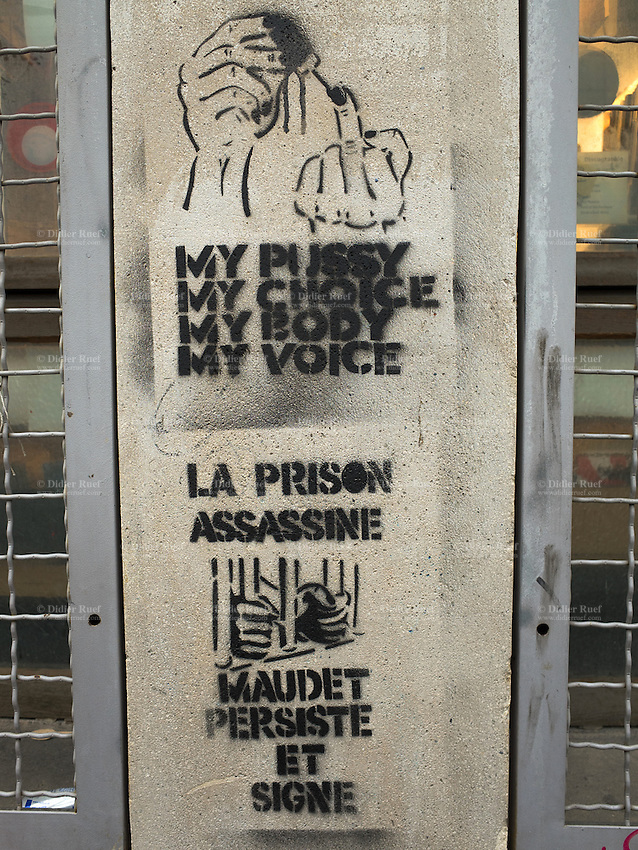 """Switzerland. Geneva. Graffiti on the wall. A person has writen the words: My pussy. My choice. My body. My voice. The graffiti contains explicit language and sexual references. Sexually explicit language. In Western culture, the finger (as in giving someone the finger or the bird, also known as the finger wave, the middle finger, flipping someone off, flipping the bird, shooting the bird, the rude finger, the one finger salute) is an obscene hand gesture. It communicates moderate to extreme contempt, and is roughly equivalent in meaning to """"fuck off"""", """"fuck you"""", """"shove it up your ass"""", """"up yours"""" or """"go fuck yourself."""" It is performed by showing the back of a closed fist that has only the middle finger extended upwards, though in some locales the thumb is extended. Extending the finger is considered a symbol of contempt in several cultures, especially Western cultures. The second drawing shows two hands on prison's bars and the text says. Prison is killing people. Maudet signs and oerseveres. Pierre Maudet is a Swiss politician, a member of FDP and a Member of the Conseil d'Etat in charge of the Department of the Security and the Economy (DSE). 12.02.2014 © 2014 Didier Ruef"""