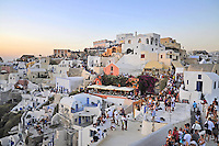 Tourists on roofs and streets of Oia watch Santorini sunset