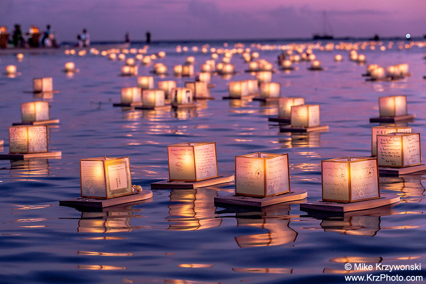 Lanterns floating in the water at sunset during the 15th Annual Lantern Floating Ceremony at Ala Moana Beach Park in Honolulu on Memorial Day