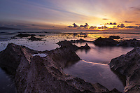 At sunset, water swirls around tide pool rocks at Shark's Cove, North Shore of O'ahu.
