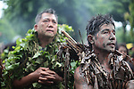 "A steady rain begins to fall, as two men sing a hymn during the annual Taong Putik, or ""mud people,"" festival in Bibiclat, on Luzon island, Philippines. The festival honors St. John the Baptist, and devotees cover themselves with mud, banana leaves and vines to symbolize the animal skins the saint wore in the Bible. June 24, 2011."