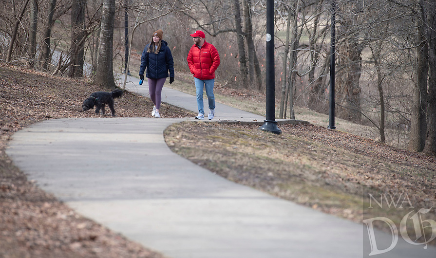 Elizabeth Parsley and Cole Brainerd, both of Fayetteville, walk their dog Sherman Sunday Jan. 10, 2021 on a trail in Wilson Park in Fayetteville. The National Weather Service is calling for high temperatures on the 50s this week. Visit nwaonline.com/210111Daily/ and nwadg.com/photos. (NWA Democrat-Gazette/J.T. Wampler)
