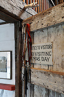 A pair of dog leads hangs on a nail on the back of a rustic door