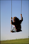 young girl playing on swing