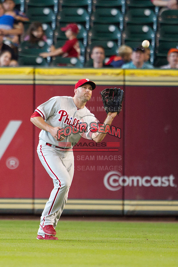 Philadelphia Phillies outfielder Nate Schierholtz #22 makes a catch during the Major League baseball game against the Houston Astros on September 16th, 2012 at Minute Maid Park in Houston, Texas. The Astros defeated the Phillies 7-6. (Andrew Woolley/Four Seam Images).
